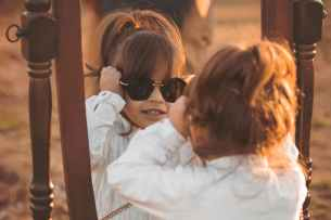 girl in white long sleeved shirt wearing sunglasses facing mirror